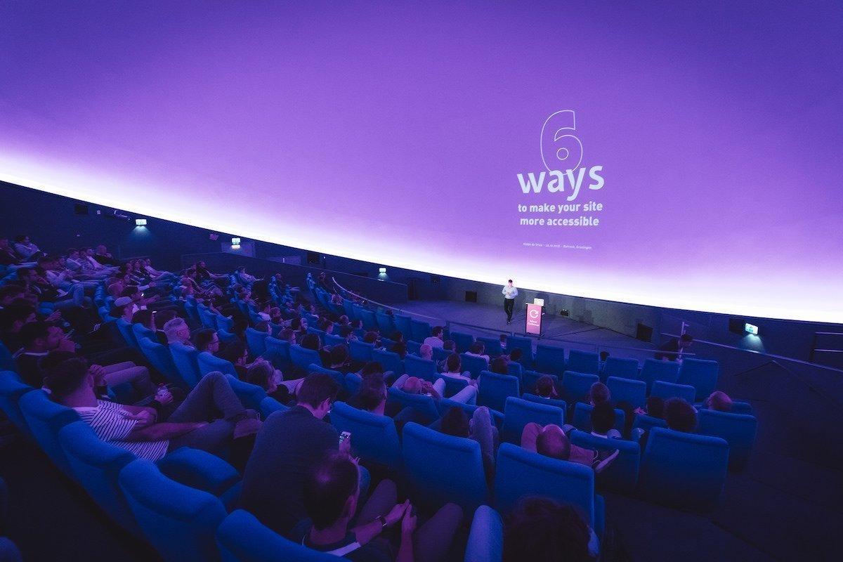 Uitzicht vanuit de zaal op de spreker Hidde de Vries met daarachter de slide '6 ways to make your site accessable'